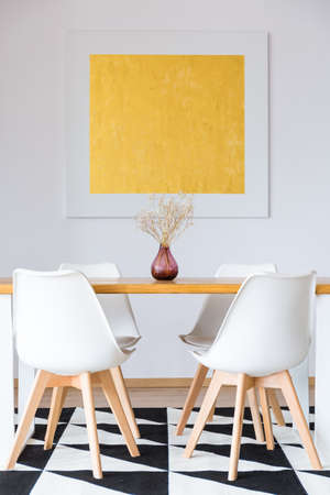 Set of four white chairs standing by the table on a black and white rug in a dining room interior