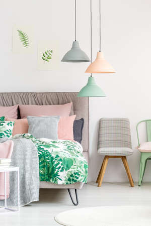 White room with bed, chairs, drawings and lamps in pastel colors