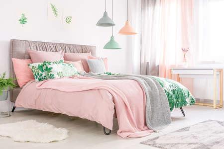 Cama tamaño king con cabecera suave y ropa de cama rosa pastel en habitación femenina con ventana