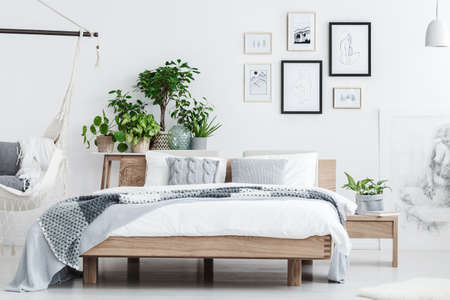 Wooden bed with white bedding, grey cushions and knit blanket standing in white bedroom with plants and hammock Stock Photo