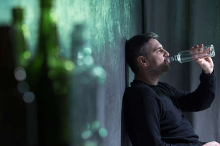 Man wearing black clothes drinking alcohol from transparent bottle alone Stock Photo