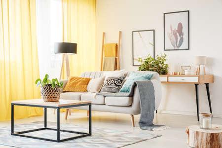 Plant op de tafel en lamp in warme woonkamer met gele gordijnen, posters en kussens op de bank Stockfoto