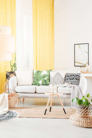 Plant on pouf and cushions on settee in warm bohemian living room with stool on carpet