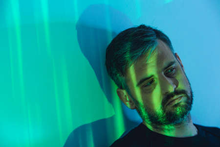 Sad caucasian man leaning against the wall in a room with colorful lights