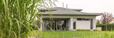 Zicht op het grijze familiehuis omgeven door goed onderhouden gazon