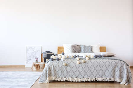 Poster lying next to a double bed with white, beige and gray cotton balls on it Reklamní fotografie