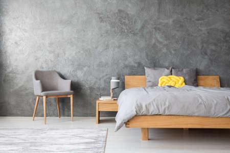 Grauer Innenraum eines geräumigen einfarbigen Schlafzimmers mit einem gelben Kissen, das auf einem Königgrößenbett liegt Standard-Bild