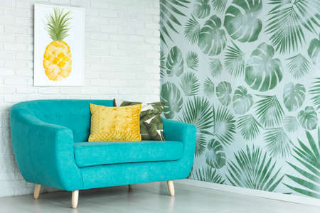 Yellow pillow on blue sofa against a wall with pineapple poster in living room with floral wallpaper