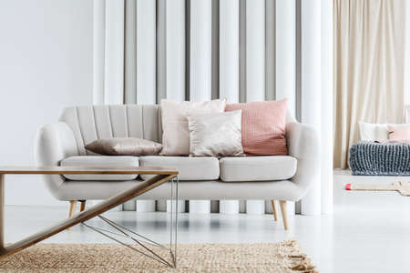 Bright grey couch with cushions and wooden table standing in white living room Stock Photo - 91668347