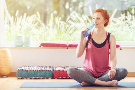 Woman drinking water, sitting on a blue exercise mat after a pilates class in the gym Stock Photo
