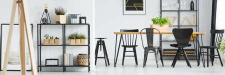 木製家具付きの明るいダイニングルームのダイニングテーブルの棚と黒い椅子の植物