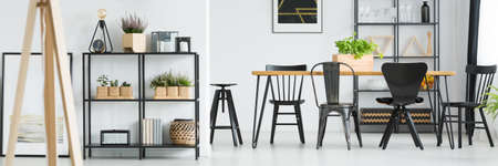 Plants on shelf and black chairs at dining table in bright dining room with wooden furniture