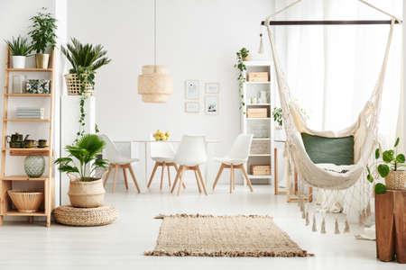 Chaise brésilienne suspendue à l'intérieur de la salle à manger blanche avec tapis, plantes en pot et affiches au mur