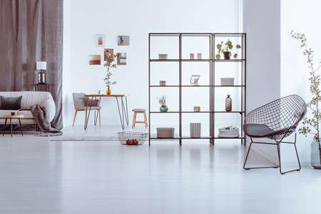 선반, 베이지 색 소파 및 테이블에 장식 된 넓은 거실에 디자이너 의자