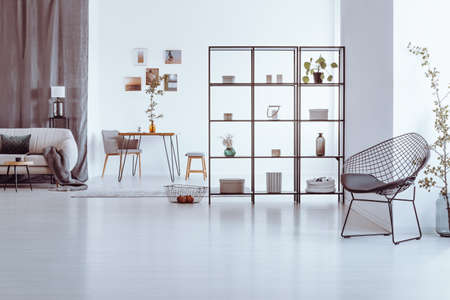 Designer chair in spacious living room with decorations on shelves, beige sofa and table