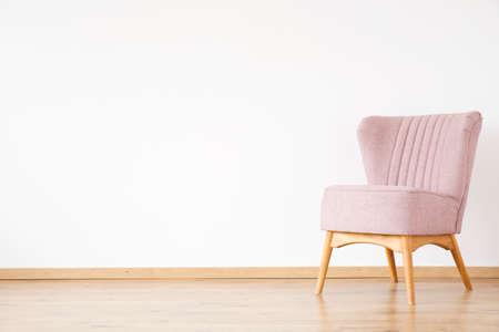 空のリビングルームにコピースペースを持つ白い壁に対するピンクのアームチェア