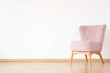Pink armchair against white wall with copy space in empty living room