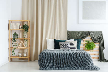 Wooden rack with potted plants, books and decorations standing in the corner of bright room with bed and handmade knit blanket Reklamní fotografie