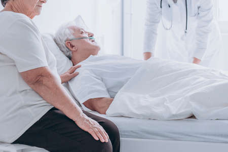 Doctor and family member supporting dying senior man lying in bed at the hospital
