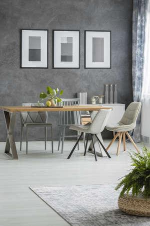 食器棚にポスターや装飾が施された灰色の壁に対してテーブルに椅子が付いている古典的なダイニングルーム 写真素材