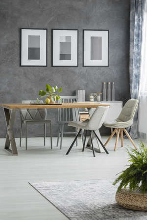 Classic dining room with chairs at table against grey wall with posters and decorations on cupboard