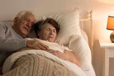 自宅で痛みに苦しむ彼の死にかけている妻の世話をするシニア男性