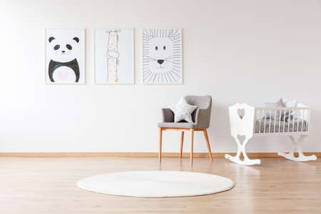 Grey chair with pillow and white round rug near white crib in baby's room with animal posters on the wall