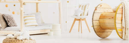 Panorama of simple bright baby room in open white apartment with cozy pillows on DIY bed and large wooden spool decoration