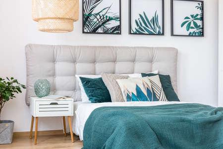 Rattan Lampe über weißem Schrank mit grüner Vase neben Bett mit gemusterten Kissen und grüne Decke im Schlafzimmer Interieur Standard-Bild - 91680253