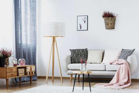Mand met heide en poster op witte muur in eenvoudige woonkamer interieur met lamp, bank, kast en tafel