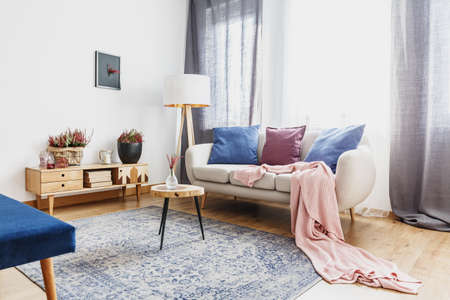 Wooden stool with glass vase on patterned carpet next to sofa with pink blanket in cozy living room interior with rustic cupboard