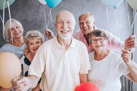 Sorrindo, homem idoso, e, seu, amigos, com, balões, desfrutando, seu, partido aniversário Foto de archivo - 91657608