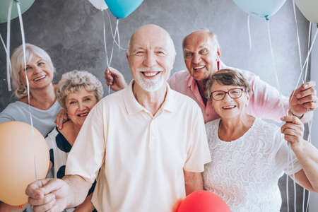 Smiling elderly man and his friends with balloons enjoying his birthday party Archivio Fotografico
