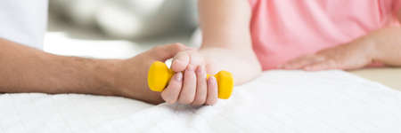 Close-up of physiotherapist supporting patient while exercising with yellow dumbbell