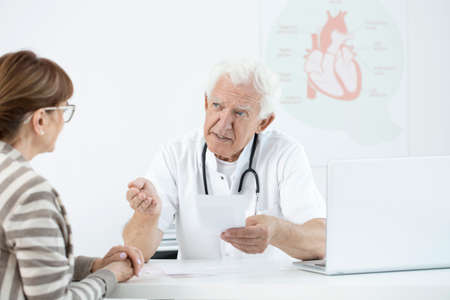 Senior doctor consulting possible side effects after surgery with a patient in his office