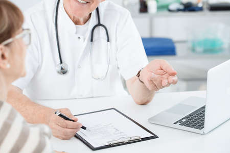 Close-up of smiling surgeon with stethoscope consulting good tests results with a patient