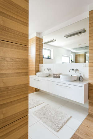 Large spacious bathroom finished in wood with mirror and sink Stok Fotoğraf