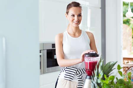 Healthy vegetarian woman preparing energetic red cocktail in white modern kitchen