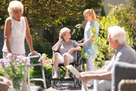 Mulher sênior em cadeira de rodas, passar o tempo fora, recebendo um pouco de ar fresco com a enfermeira da casa de repouso