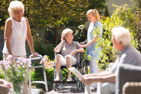 Senior donna in sedia a rotelle trascorrere del tempo fuori, ottenendo un po 'd'aria fresca con la sua infermiera dalla casa di riposo