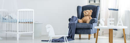 Teddy bear sitting on a navy blue armchair close to a childs bed in a newborn room interior