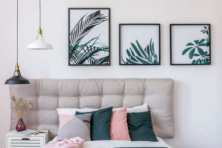 Pastelkleuren op bed en lampen boven witte kast met vaas in helder slaapkamerinterieur met bloemenaffiches