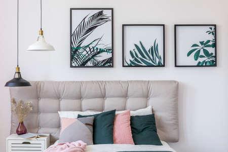 Pastellkissen auf Bett und Lampen über weißem Kabinett mit Vase im hellen Schlafzimmerinnenraum mit Blumenplakaten Standard-Bild - 91680368