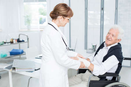 Smiling elderly patient grateful for help of a doctor in white uniform fixing his hand Stock Photo