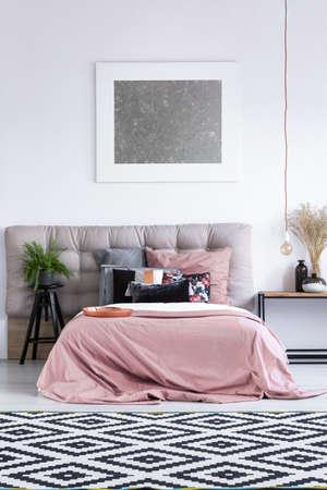 Patterned black and white carpet in elegant bedroom interior with modern artwork, pink bedding and fern plant