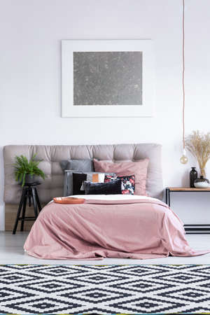 Patterned black and white carpet in elegant bedroom interior with modern artwork, pink bedding and fern plant