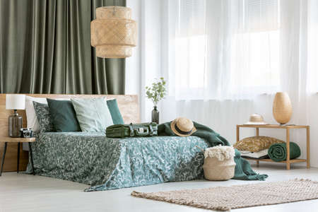 帽子とキングサイズのベッドにスーツケース、籐製ランプ、寝室のインテリアのスツールの上にカメラ