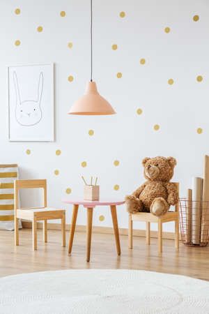 테이블과 벽에 포스터 위에 복숭아 램프와 아늑한 아이의 방에 작은 나무의 자에 테 디 베어 스톡 콘텐츠