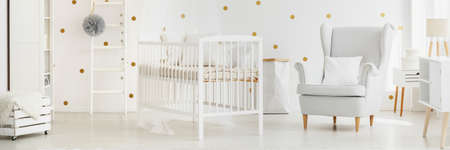 Polka dot wall decor in functional interior of white baby nursery with pastel gray armchair next to simple bed Stock Photo