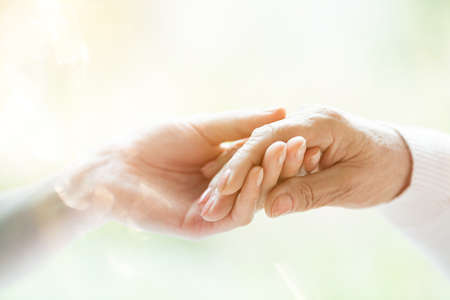 Close-up of young person's hand holding elderly person's hand as sign of caring for seniors 스톡 콘텐츠